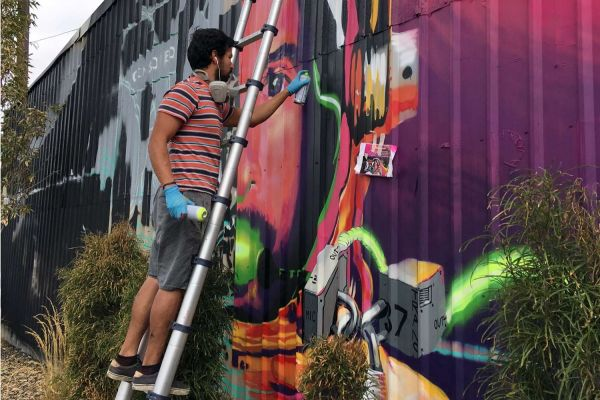 Artist Chris Fonseca installing a mural in the Live-Work-Create District in Garden City, Idaho.